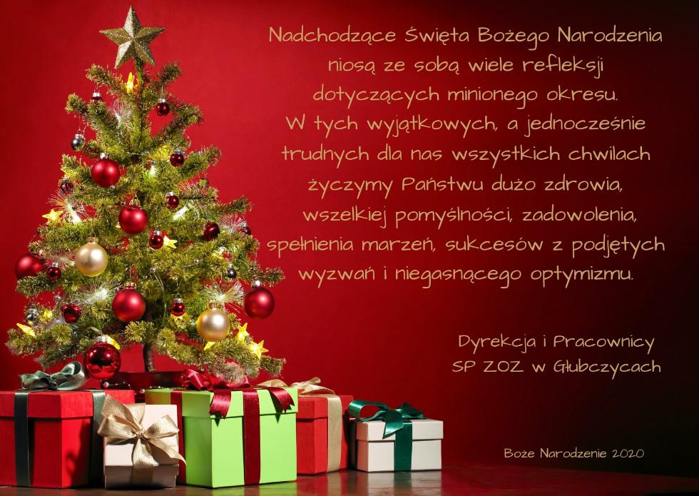 Kartka prostokątna z życzeniami na Boże Narodzenie. Na czerwonym tle po lewej stronie znajduje się choinka przystrojona różnokolorowymi bombkami, na wierzchołku jest złota gwiazda. Pod nią znajdują się prezenty. Po prawej stronie wpisany jest tekst życzeń.